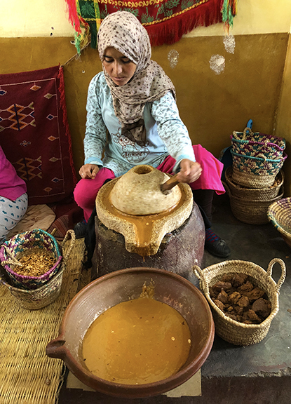 A beautiful young woman grinding the nut of the Argon tree into oil for making cosmetics and natural beauty products.