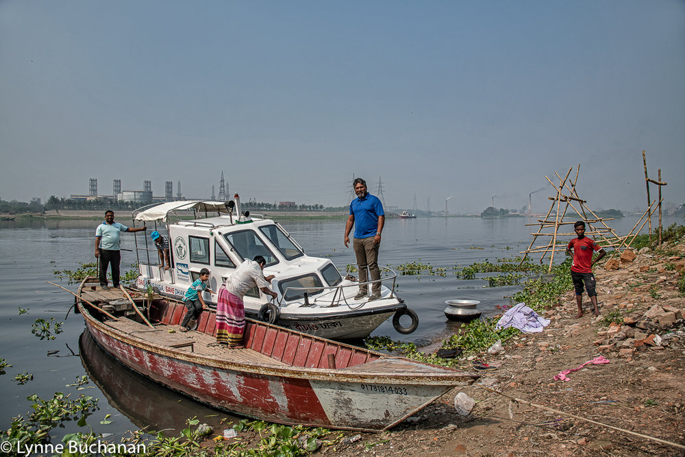Sharif Jamil ont he Bow of the Buriganga Riverkeepers Boat