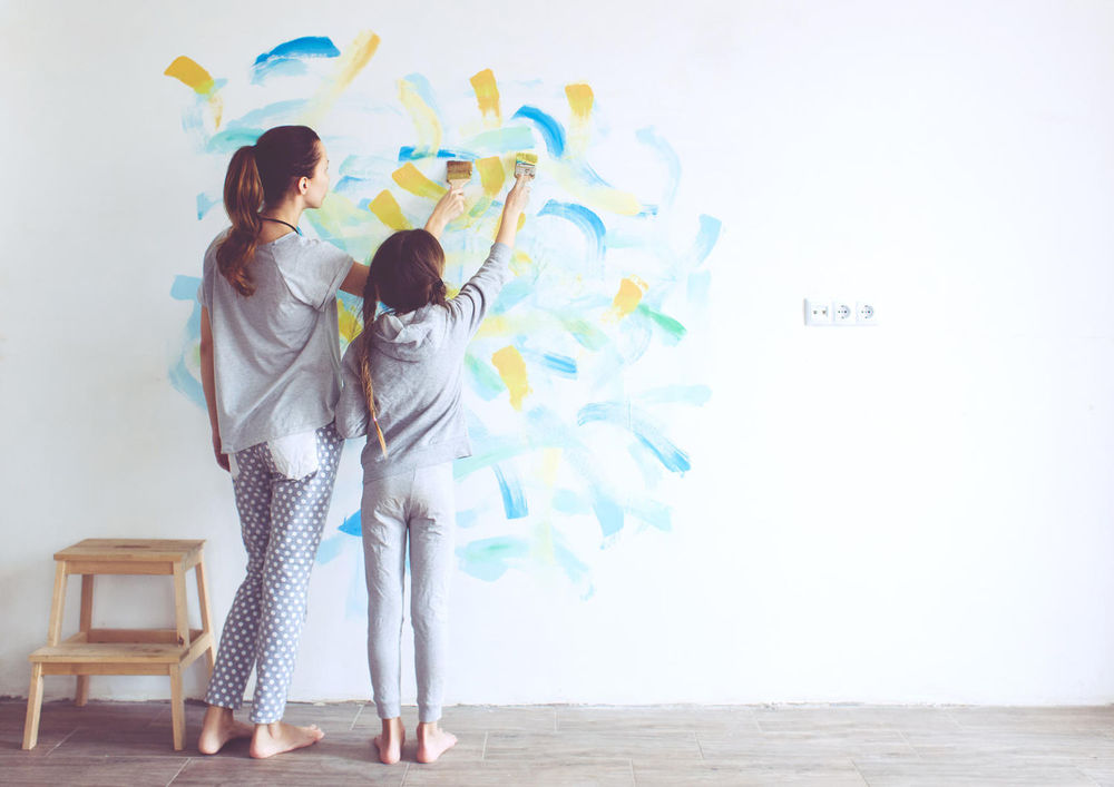 single mom and daughter painting wall