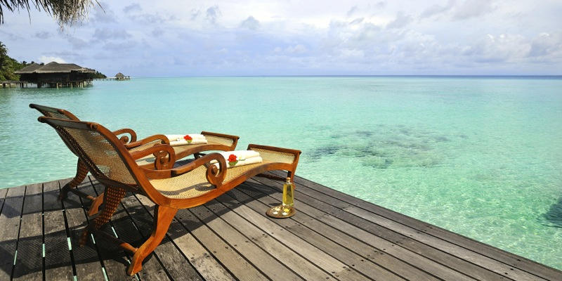 lounges on a deck overlooking a beach