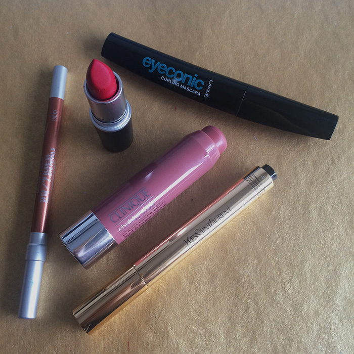From Left To Right: 1) Urban Decay 24/7 Glide-On Pencil In 'Lucky', 2) MAC Lipstick In 'Ruby Woo', 3) Clinique Chubby Stick Cheek Colour Balm In 'Amp'd Up Apple', 4) Yves Saint Laurent Touche Eclat Highlighter, and 5) Lakme Eyeconic Curling Mascara