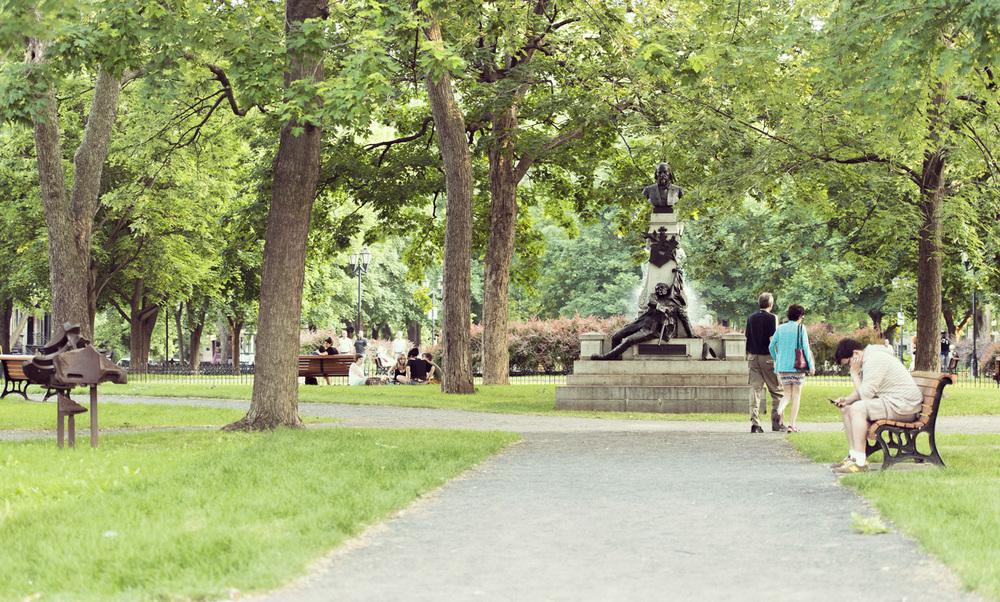 Des piétons passent à côté du  Monument à Louis-Octave Crémazie  (1906) de Louis-Philippe Hébert, au square Saint-Louis. © Denise Caron
