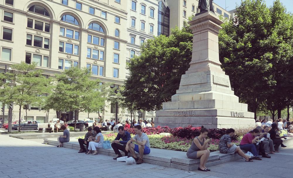 Des travailleurs sont assis et pique-niquent sur le muret entourant le  Monument à la reine Victoria  (1869) de Marshall Wood, au square Victoria. © Denise Caron