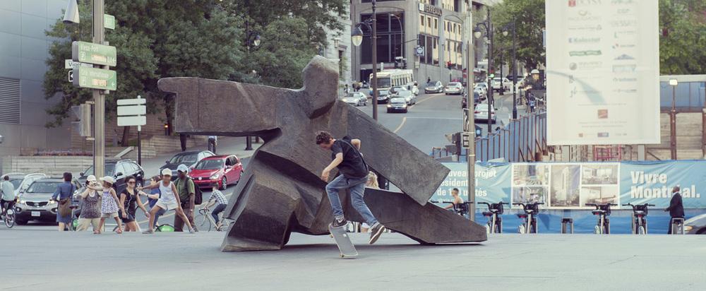 Un adolescent fait du skateboard devant  Taichi Single Whip  (1985) de Ju Ming, qui est installée au square Victoria, alors qu'un enfant imite la pose de la sculpture à l'arrière-plan, à gauche. © Denise Caron