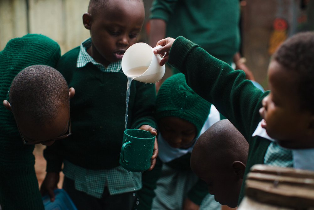 Elementary students work together to wash their mugs after eating their morning porridge.