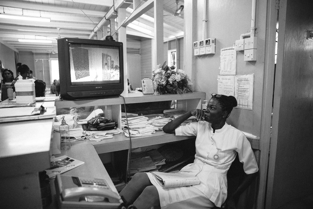 A maternity ward nurse watches television while waiting for her patients to go into active labor at West Demerara Hospital.