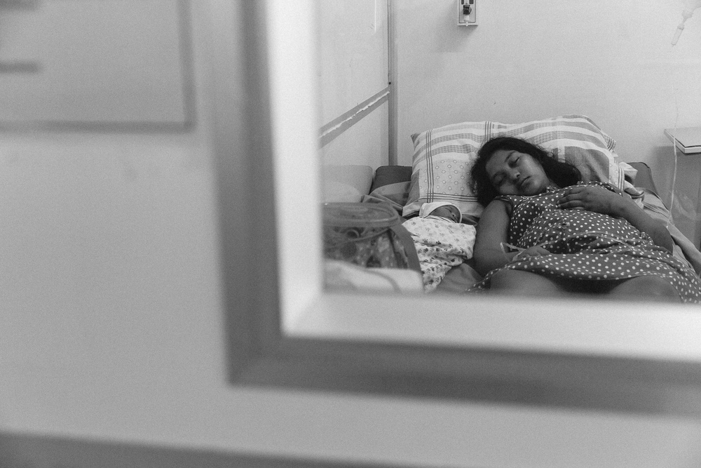 A mother and child rest in a recovery room after a tiring birth at Georgetown Public Hospital.