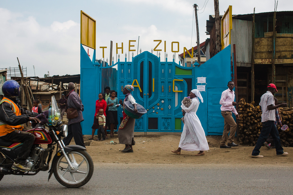 The AIC Zion compound is protected by tall walls and an elaborately decorated metal gate.