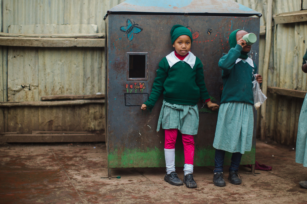 Girls finish their porridge and wait for class to begin in the morning.