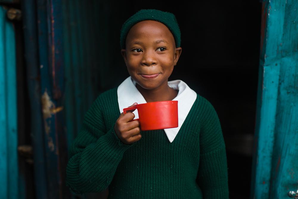 An elementary student drinks her morning porridge as a part of the school's feeding program.