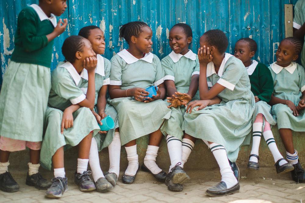 Girls enjoy their lunch break together in the school's courtyard.