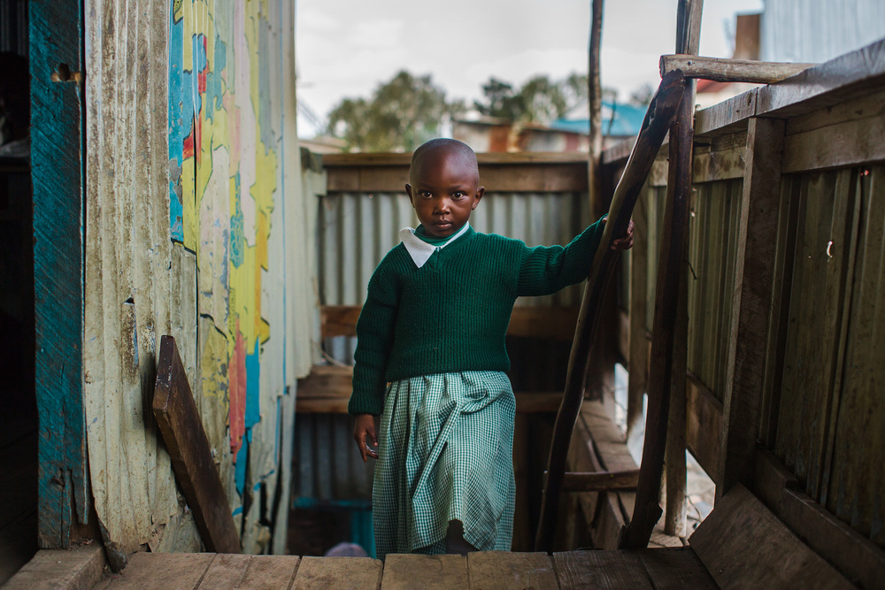 A girl pauses for a portrait on her way back to class after using the school's bathroom facilities - a toilet is a luxury she does not have at home. AIC Zion has one of the only bathroom facilities with running water in the whole slum.