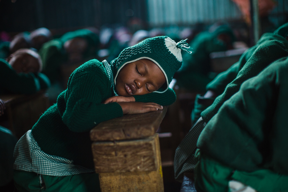 A child sleeps on his desk during the preschool class' nap time.