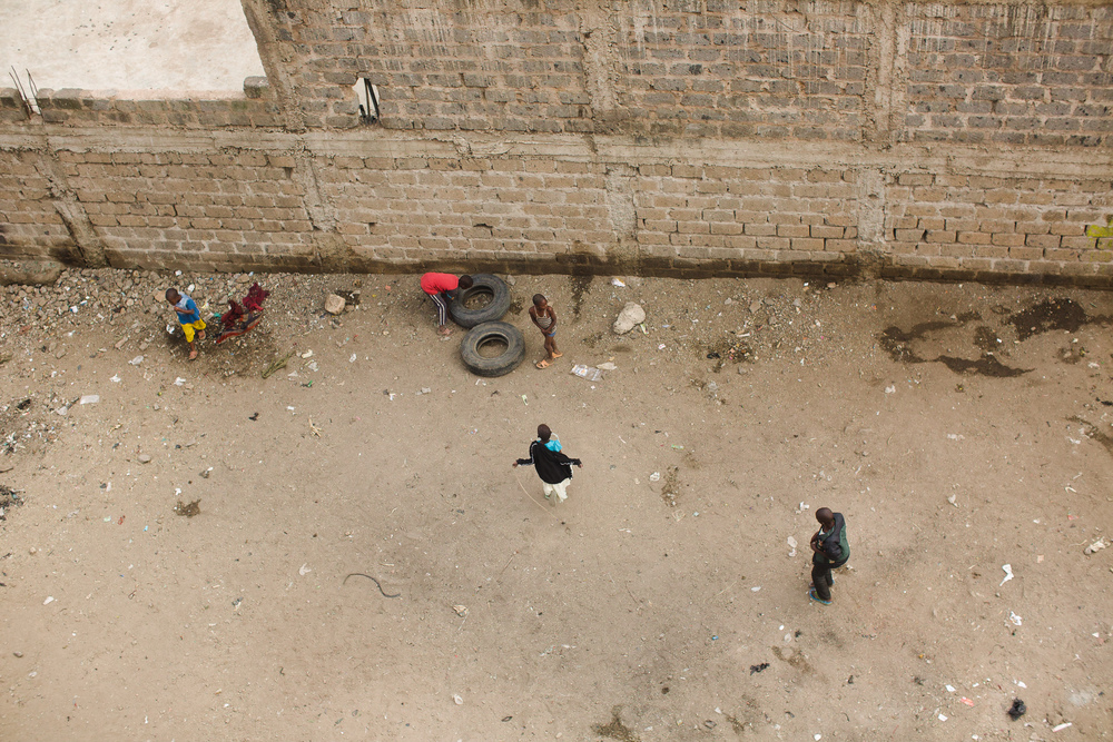 Children play with tires and string in a rare open space in the slum.