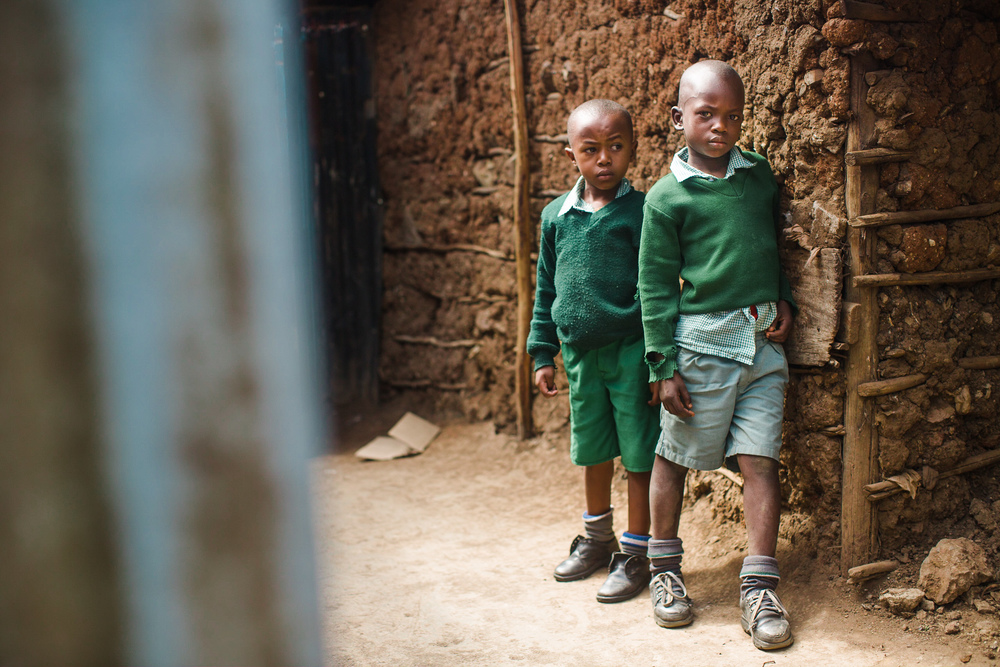 Boys stand against a neighboring house build from mud, sticks, and corrugated metal.