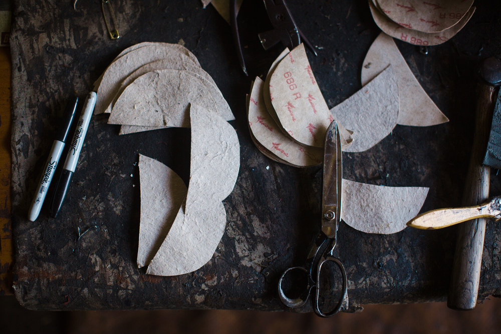 Tools and shoemaking materials rest on a table in the Sole Hope shoemakers' workshop.