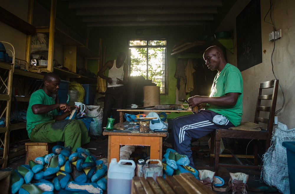 Sole Hope shoemakers work in their workshop to finish shoes before a school clinic.
