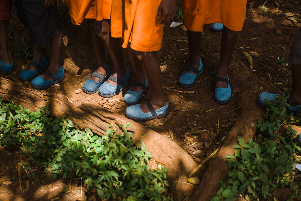 School children stand under a tree after having their feet examined and being given new shoes at a Sole Hope clinic at their school.