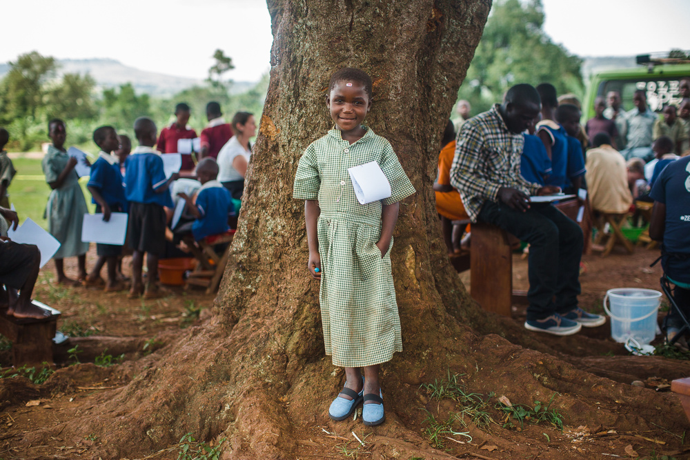 A girl poses for a portrait by a clinic at her school with new shoes on her feet, jigger prevention information pinned to her uniform, and a few treats for her bravery during the jigger removal process.