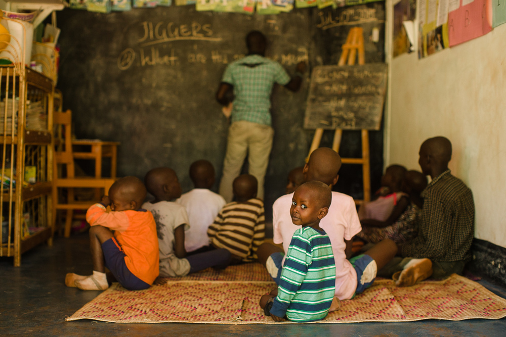 Children sit in a classroom at the Sole Hope classroom to learn about safe jigger removal and jigger prevention.