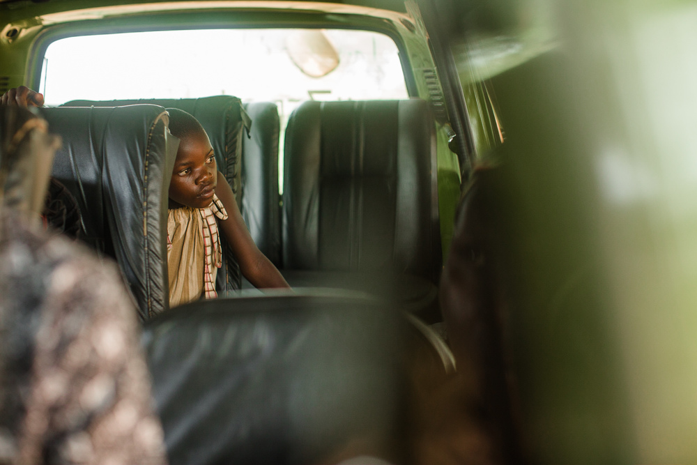 After a week at the Sole Hope Outreach House being treated for a severe case of jigger wounds, a young girl waits in the van to be driven back to her family home.