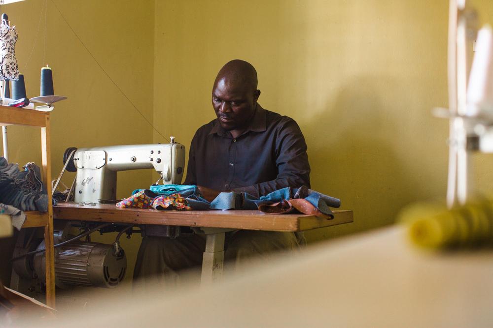 Okello, a Sole Hope tailor, sews donated denim into shoes to be given to children at a jigger removal clinic.