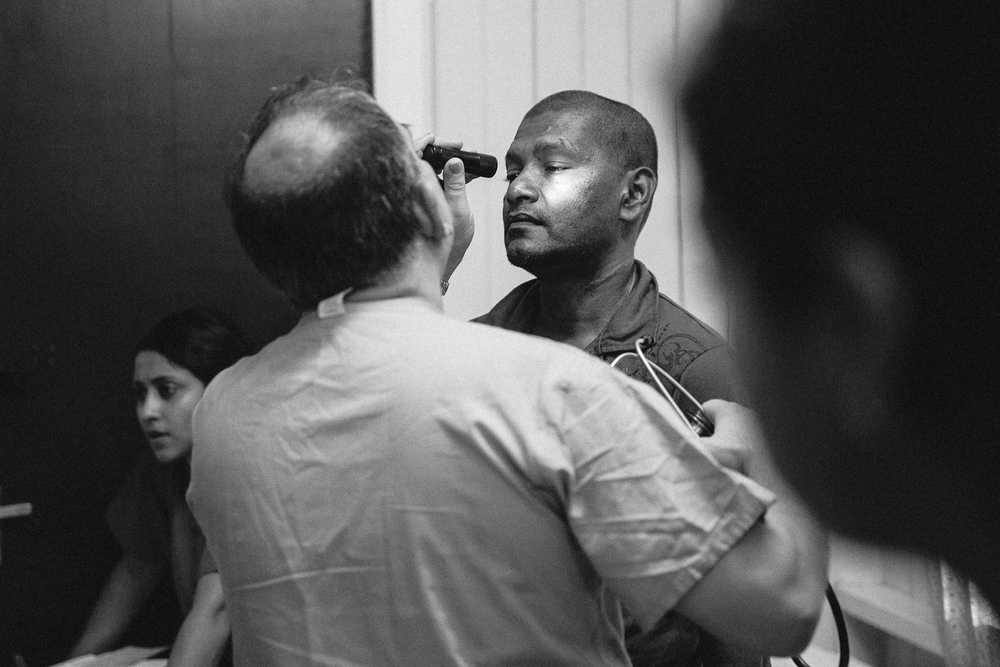 A Doctors International Anesthesiologist examines a patient in a clinic the day before his surgery at West Demerara Hospital.