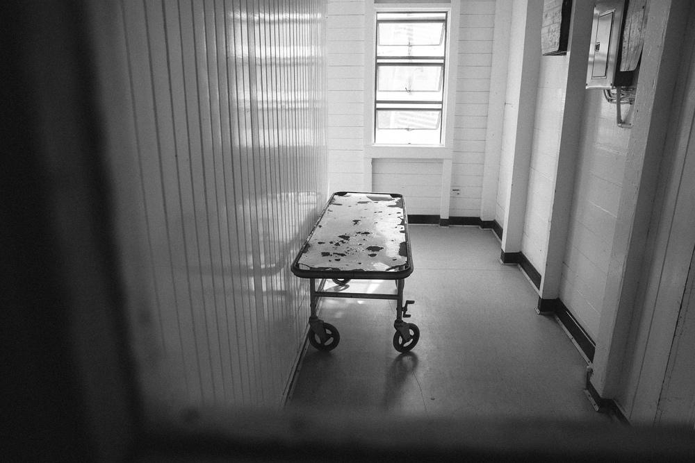 A hospital gurney waits in a hallway at West Demerara Hospital.