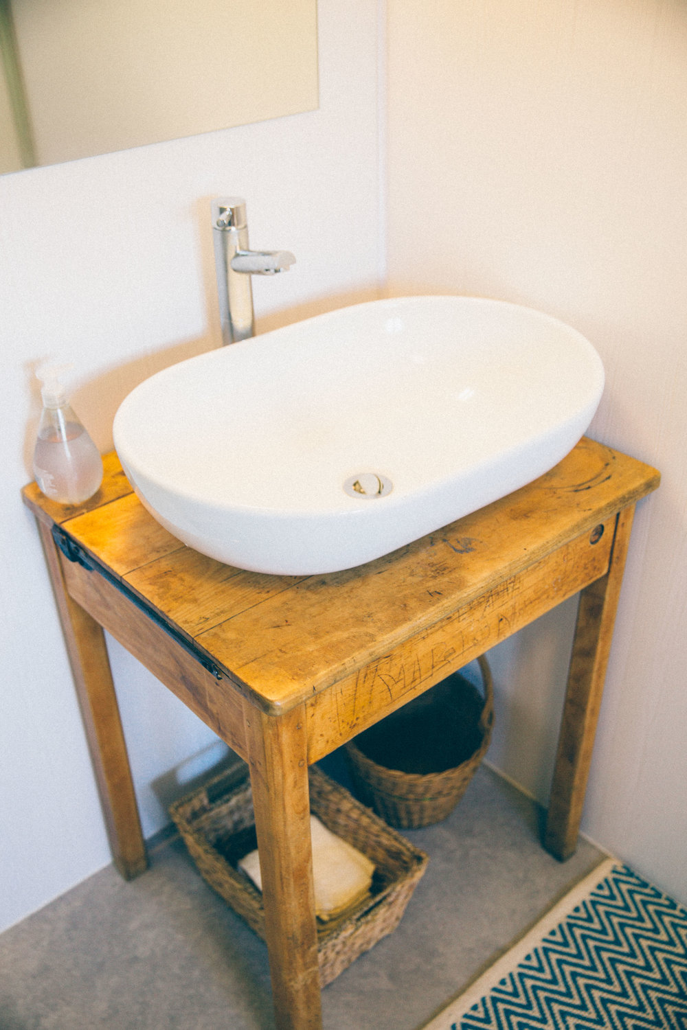 Wash bowl sink on an old school desk with baskets for flannels underneath