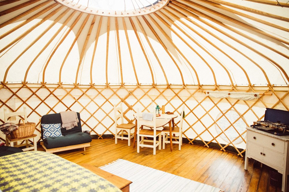 Yurt furnishings including futon, dining table and chairs, kitchen area and the end of the bed with a view out the window