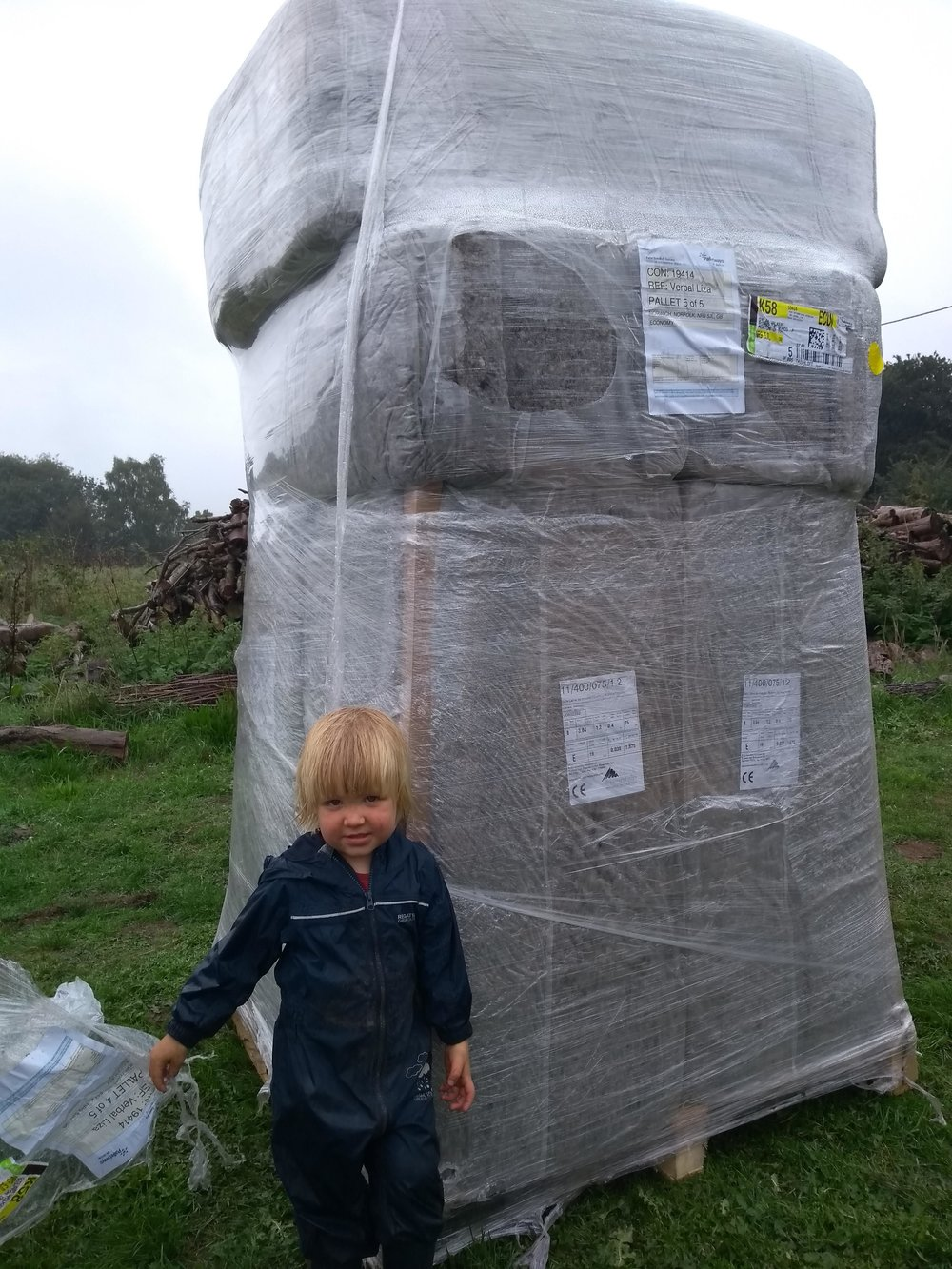 Sheeps wool natural insulation delivery with the boys helping to move it under cover
