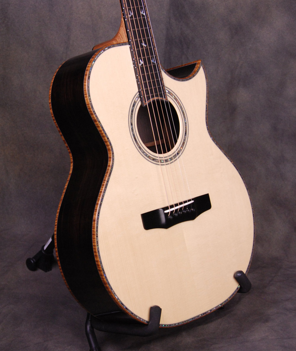 Florentine cutaway, Euro Swiss Spruce top, African Blackwood back/sides, 3-ring Abalone rosette, Koa binding, Abalone top trim, Koa trimmed ebony fingerboard, Charis Doves In Flight fingerboard markers.