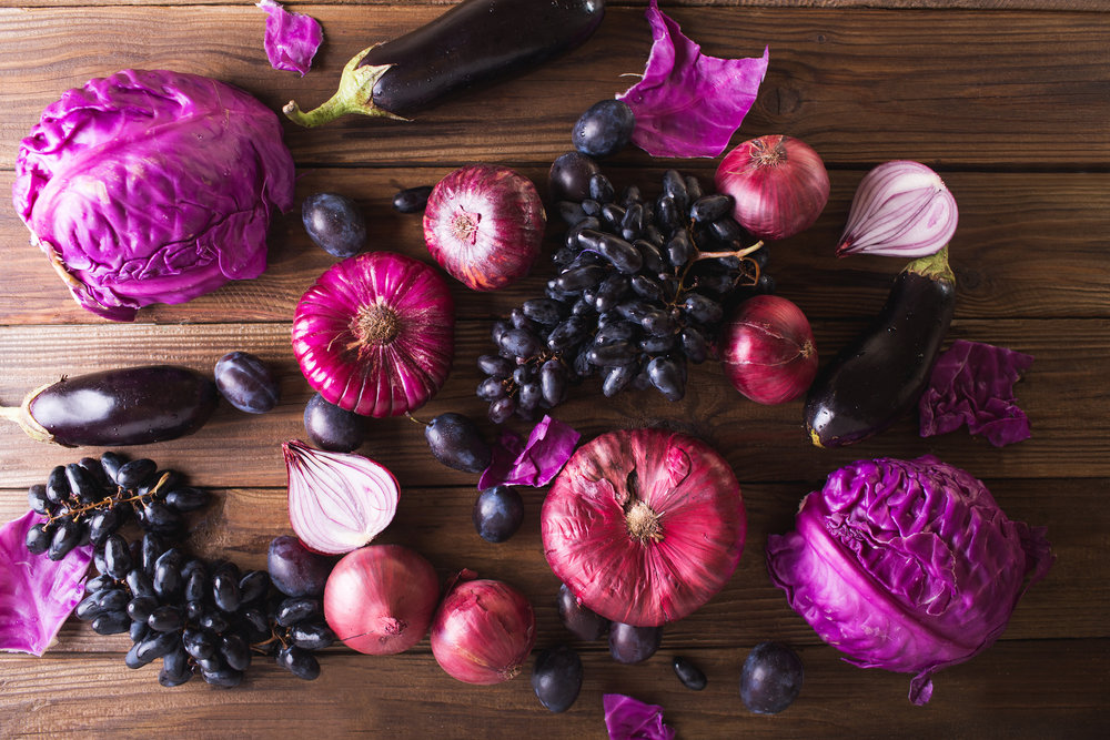 Purple fruits and vegetables. Blue onion, purple cabbage, eggplant, grapes and plums on a wooden background.