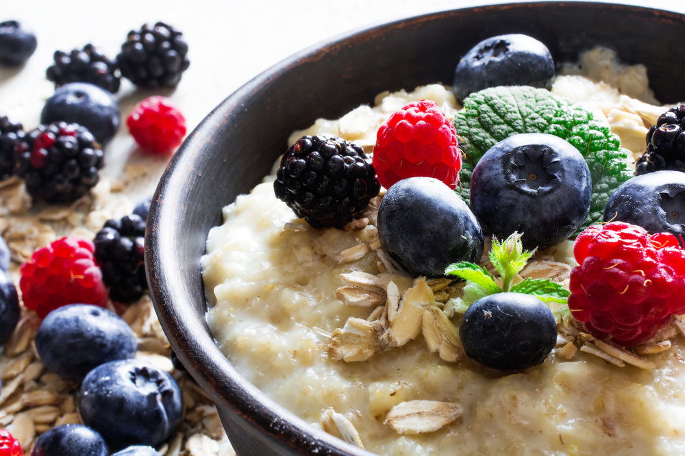 oatmeal porridge in ceramic bowl with fresh ripe berries
