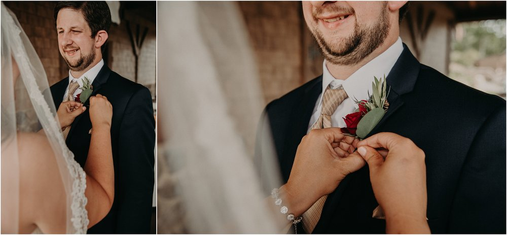 Bride pins groom's bouquet onto his suit lapel