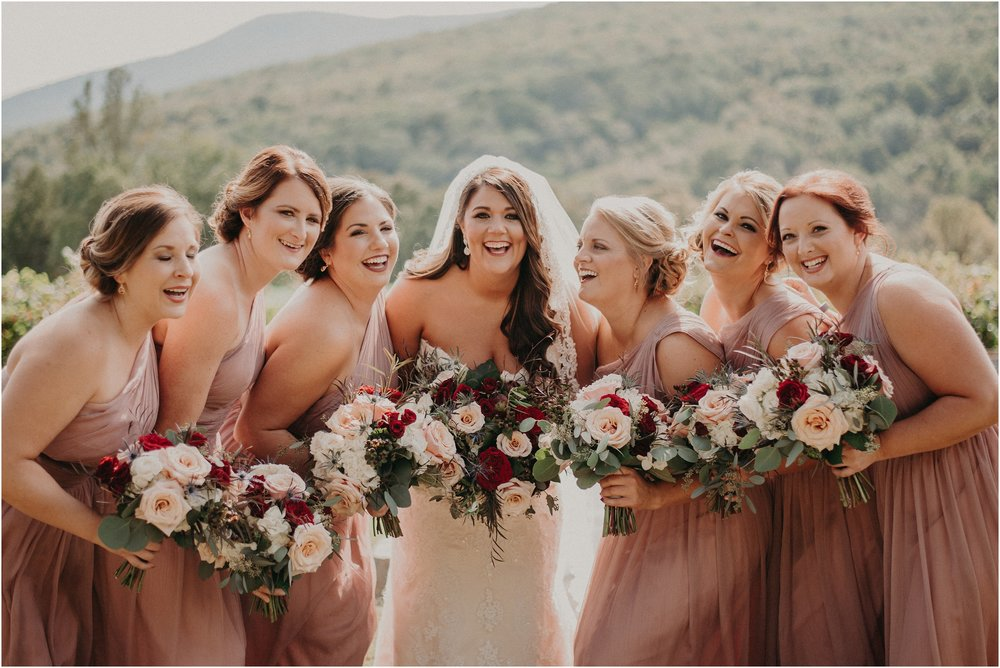 Bride and bridesmaids laugh together on wedding day