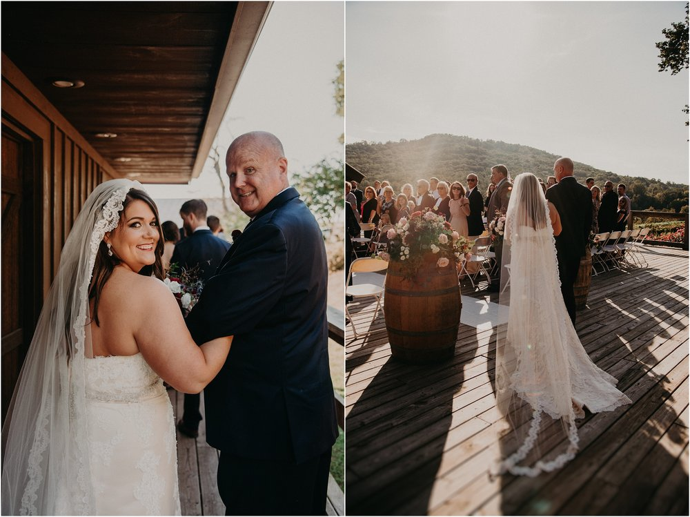 Father of the bride walks bride down the aisle on vineyard deck