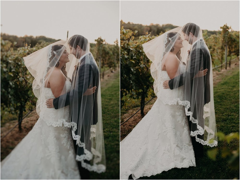 Wedding couple get cozy together beneath bride's cathedral veil