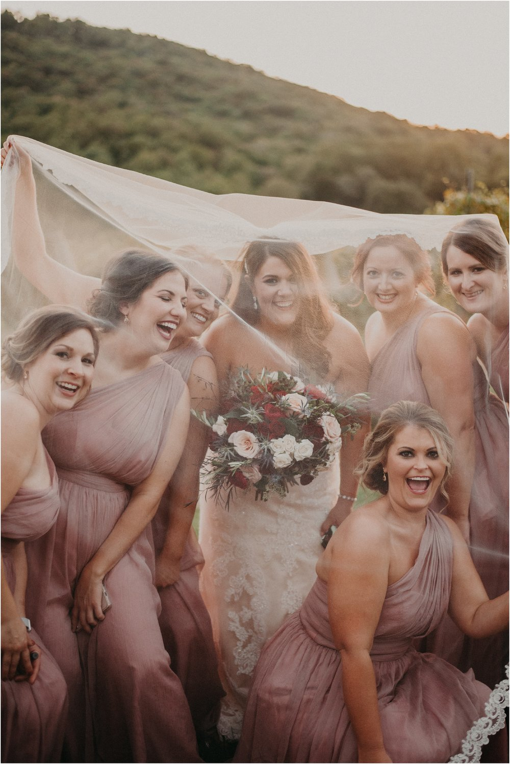 Bride and bridesmaids laugh together underneath cathedral veil