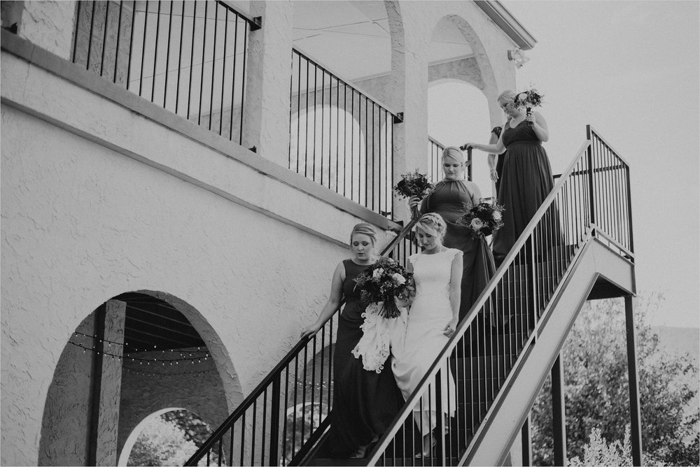 Bride and bridesmaids descend stairs of villa
