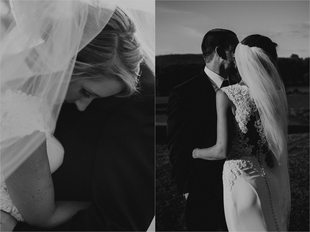 Bride embraces her groom as her cathedral veils blows in the wind around them