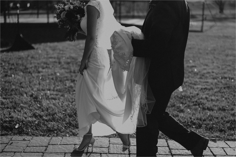 Groom holds bride's wedding dress train as they walk away