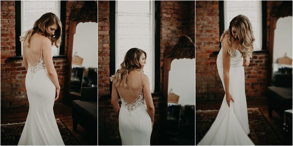 The bride smooths her wedding gown in the exposed brick bridal suite