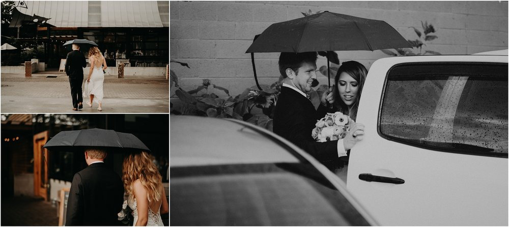 The bride and groom make their entrance to the reception at the Flying Squirrel beneath an umbrella