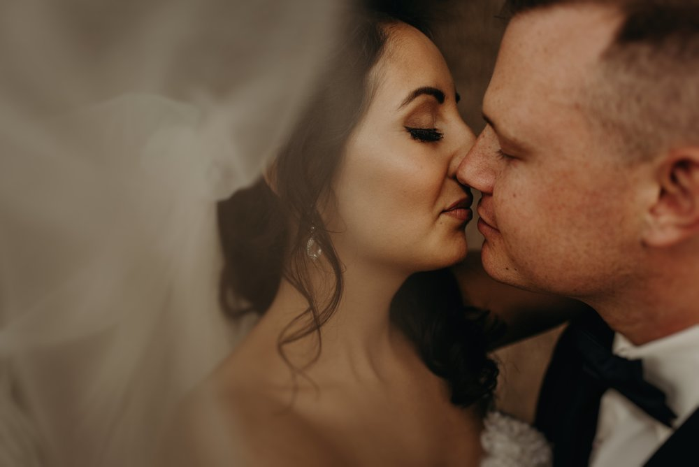 Bride and groom share a kiss beneath bride's wedding veil in Gatlinburg, Tennessee