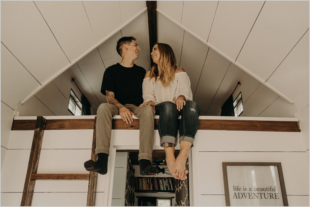 Couple sits together on the ledge of their loft bedroom in their tiny home photo session