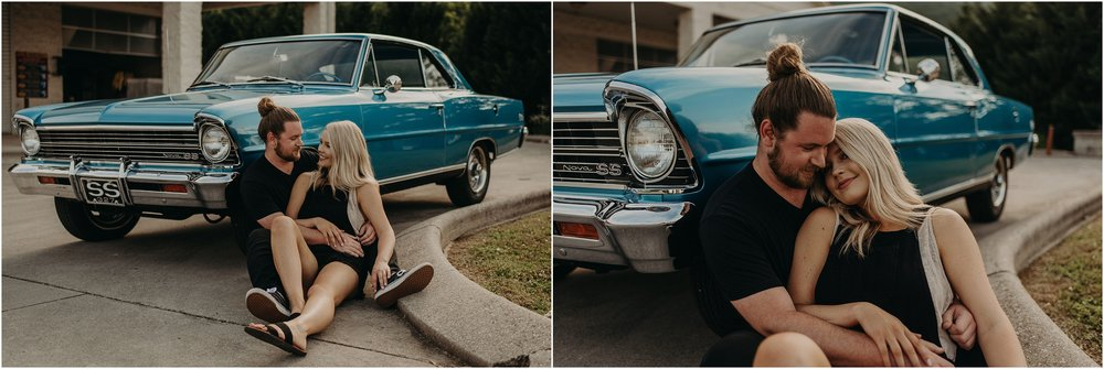 Couple sits together in the parking lot in front of a Chevy Nova SS