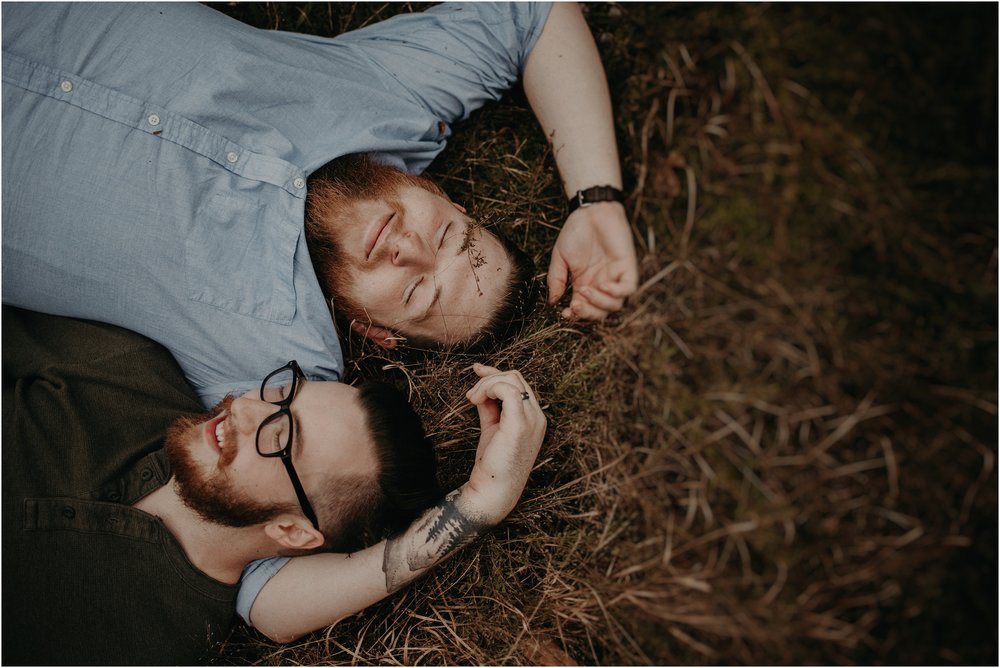 LGBTQ love story photo session with couple laying in field