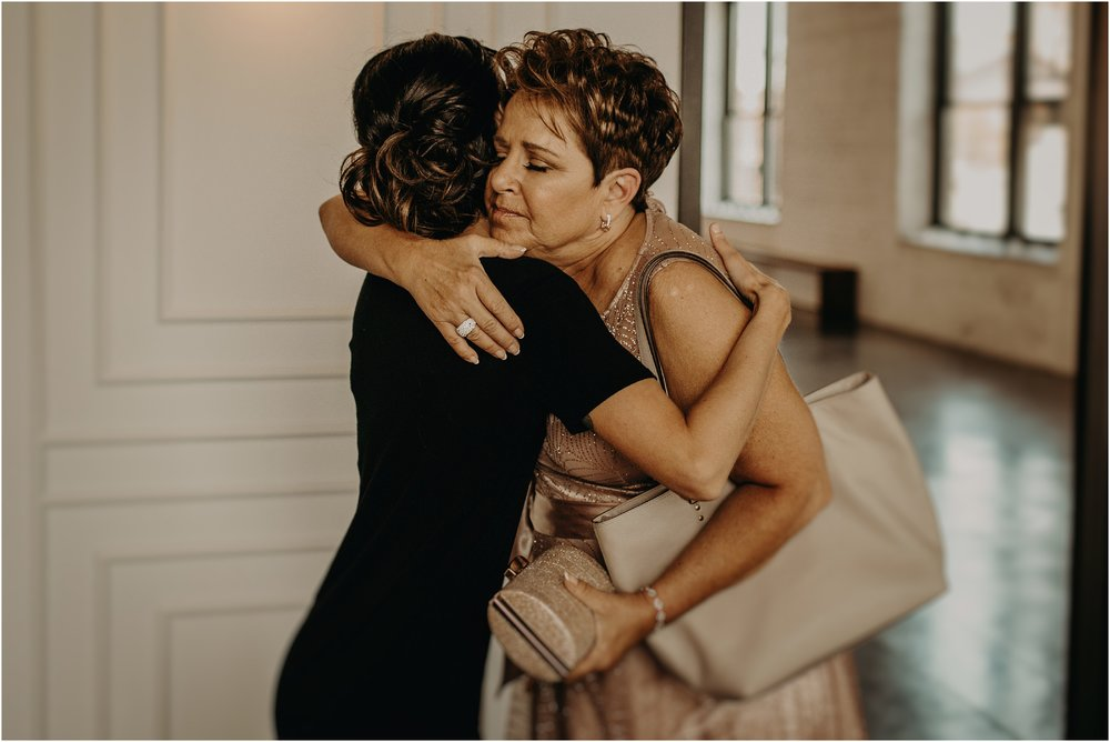 Bride embraces her mother in the wedding suite