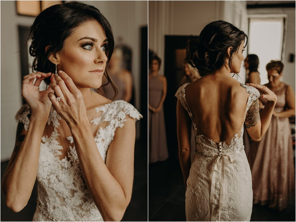 The bride fastens her earrings as the final touches to her chic wedding attire